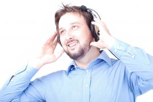 Hearphones on man's head with blue shirt