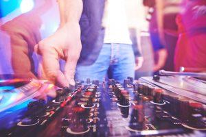 Hand of dj adjusting sound